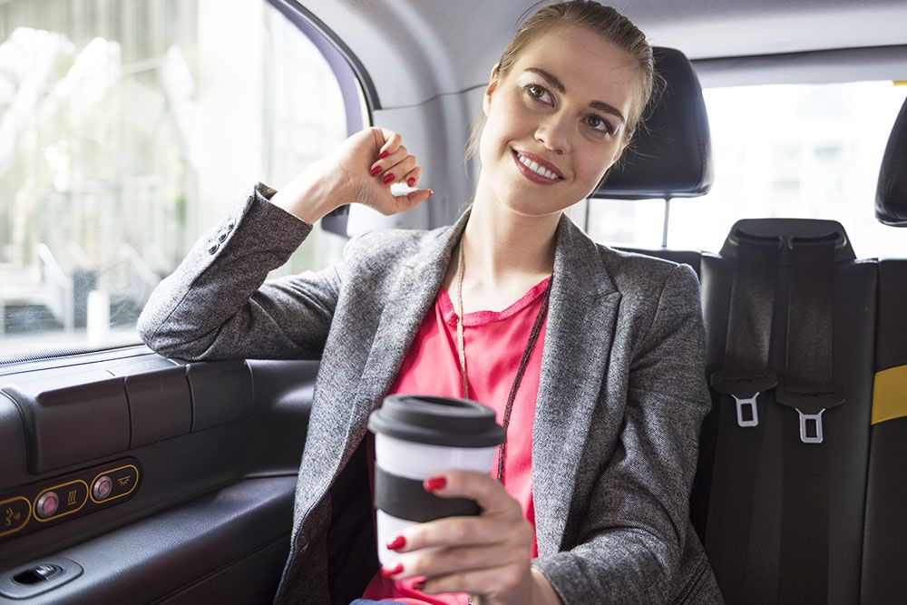 Business woman with a coffee in a taxi